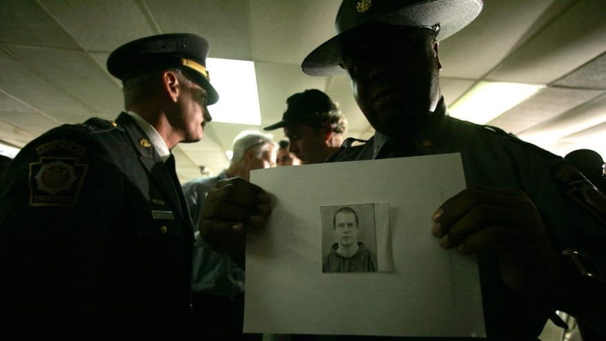 FILE - In this Oct. 2, 2006, file photo, a Pennsylvania State Police officers holds an undated handout photo of Charles Carl Roberts IV in Nickel Mines, Pa. Charles Carl Roberts IV barricaded himself inside the Amish schoolhouse near Lancaster and opened fire, killing five girls and injuring five others before committing suicide as police closed in. Terri Roberts, the mother of the gunman says she forgave her son soon after the 2006 massacre, just as the Amish themselves did.  (AP Photo/Mary Altaffer, File)