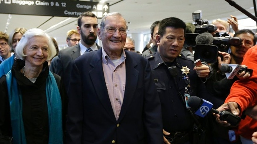 Dec. 7, 2013: Merrill Newman, center, walks beside his wife Lee after arriving at San Francisco International Airport.