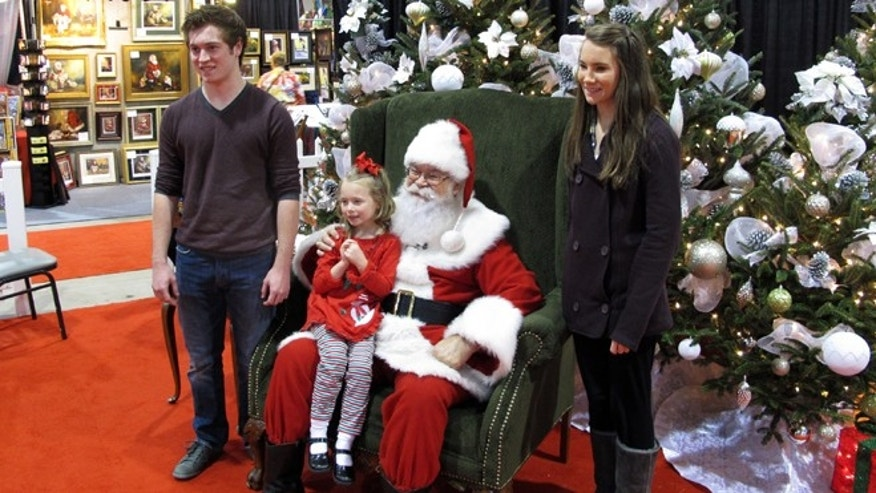 "In Nov. 29, 2013 photo taken from video, siblings Maddie, 5, Mackenzie, 15, and Caleb Bunn, 18, from Rocky Mount, N.C., pose for a photo with ""Santa"" Cliff Snider at the Christmas Carousel show in Raleigh, N.C."