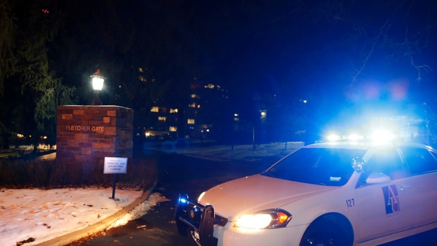 An American University police car blocks the entrance to American University at the Fletcher Gate on Wednesday night, Dec. 11, 2013, in Washington. Police and school officials say American University's campus in the nation's capital is on lockdown after police received calls about a man with a gun. (AP Photo/Alex Brandon)