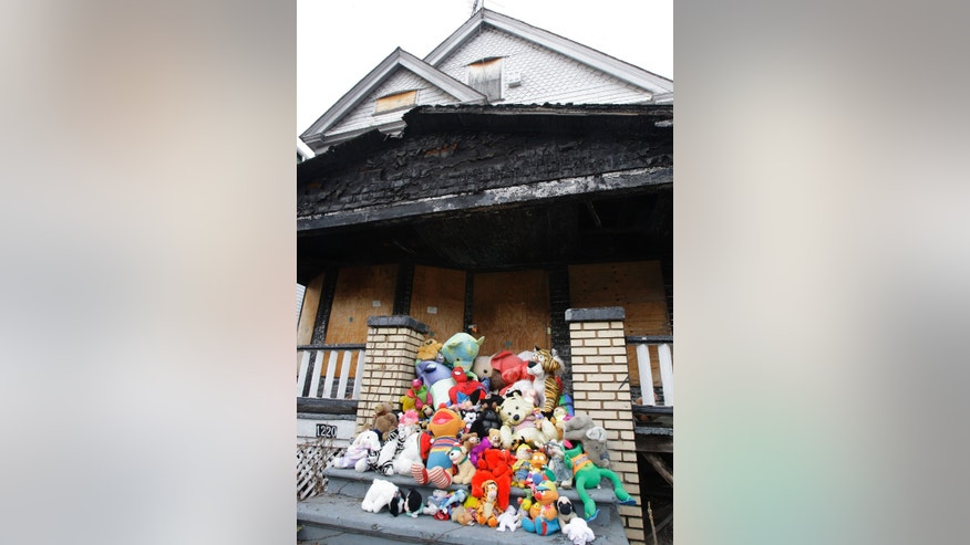 FILE - In this Friday, Feb. 10, 2012 file photo, stuffed animals are left as a memorial on the steps of the burned-out house where 9 people died in Cleveland. A November retrial has been set for Antun Lewis, the man suspected in the 2005 arson deaths of a woman and eight children at a birthday sleepover in Cleveland. Lewis' conviction at his first trial was overturned over testimony from jailhouse informants denounced by the defense as unreliable. (AP Photo/Tony Dejak, File)