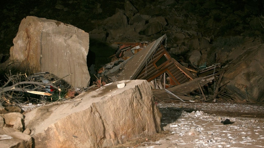 Flood lights from fire engines parked on nearby state Route 9 shine on the rubble of a two-story log home that was crushed by boulders that broke loose from the cliff above it and killed two people inside the home Thursday, Dec. 12, 2013 in Rockville, Utah. (AP Photo/The Spectrum & Daily News,  Jud Burkett)