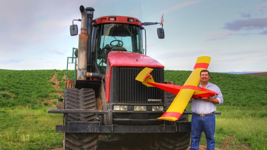 In this May 2013 photo provided by Rhonda Blair, farmer Robert Blair stands in front of his tractor holding an unmanned aircraft that he built in Kendrick, Idaho.