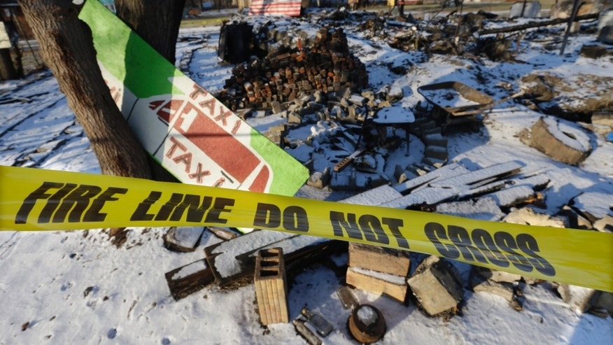 Dec. 10, 2013: In this photo taken at the Heidelberg Project in Detroit, fire tape is seen surrounding the aftermath of the fire at the House of Soul.