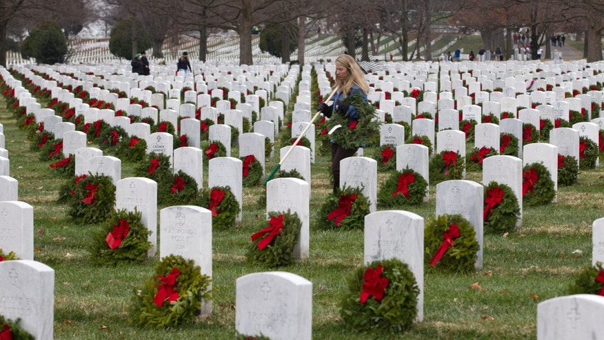 Volunteer Dotti Parker lays holiday wreaths at graves at Arlington National Cemetery in Arlington, Va., Saturday Dec. 14, 2013, during Wreaths Across America Day. Wreaths Across America was started in 1992 at Arlington National Cemetery by Maine businessman Morrill Worcester and has expanded to hundreds of veterans' cemeteries and other locations in all 50 states and beyond. (AP Photo/Jose Luis Magana)