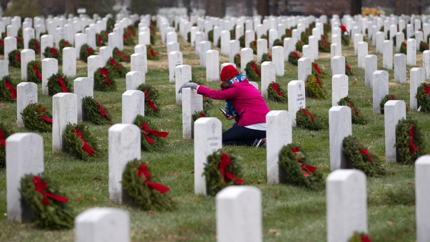 Volunteer Brandi Besecker lay a holiday wreaths at the grave of her aunt at Arlington National Cemetery in Arlington, Va., Saturday Dec. 14, 2013, during Wreaths Across America Day. Wreaths Across America was started in 1992 at Arlington National Cemetery by Maine businessman Morrill Worcester and has expanded to hundreds of veterans' cemeteries and other locations in all 50 states and beyond. (AP Photo/Jose Luis Magana)