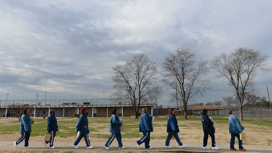 In this Dec. 13, 2013 photo, a group of inmates at the Tennessee Prison for Women in Nashville, Tenn., walk across the prison yard to get dressed for their graduation ceremony. The women earned an associates degree through Lipscomb University in a program created just for them. (AP Photo/Mark Zaleski)