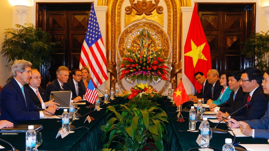 U.S. Secretary of State John Kerry, left, talks with Vietnamese Foreign Minister Pham Binh Minh, second right, in Hanoi Monday, Dec. 16, 2013.  Secretary of State Kerry is in Vietnam pressing the communist country on democratic and economic reforms and offering U.S. assistance to protect its maritime borders. (AP Photo/Brian Snyder, Pool)