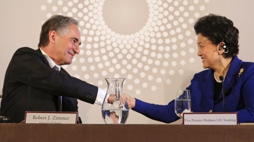 In this Nov. 18, 2013 file photo, University of Chicago president Robert J. Zimmer, left, shakes hands with Vice Premier Liu Yandong of China, after she finished her remarks at the U.S.-China University Presidents Roundtable at the University of Chicago.   Presidents at 42 private colleges scaled the $1 million annual mark in total pay and benefits in 2011, a slight bump from the year before, according to a survey based on the latest federal tax information from the 500 private schools with the largest endowments.
