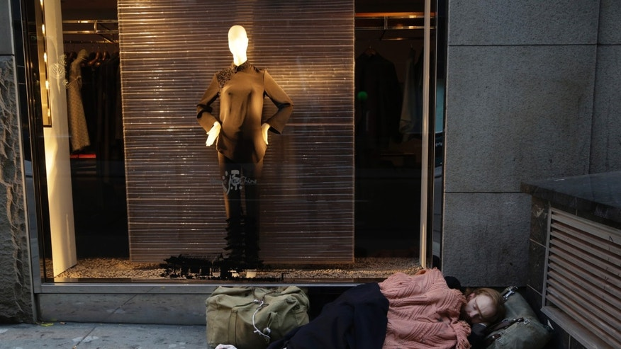 FILE - In this Wednesday, Nov. 20, 2013, file photo, a destitute man sleeps on the sidewalk under a holiday window at Blanc de Chine, in New York  The growing gap between the richest Americans and everyone else isn't bad just for individuals it's hurting the U.S. economy says a majority of more than three dozen economists surveyed in December 2013 by The Associated Press. (AP Photo/Mark Lennihan, File)