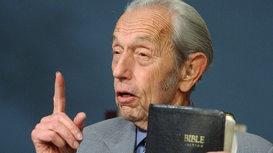 In this Dec. 12, 2002 file photo, Harold Camping holds a Bible as he speaks during his live television broadcast in San Leandro, Calif. Camping, who used his evangelical ministry and thousands of billboards to broadcast the end of the world and then gave up public prophecy when his date-specific doomsdays did not come to pass, has died at age 92. Camping died at his home Sunday, Dec. 15, 2013 according to Family Radio Network marketing manager Nina Romero. She said he had been hospitalized after falling.