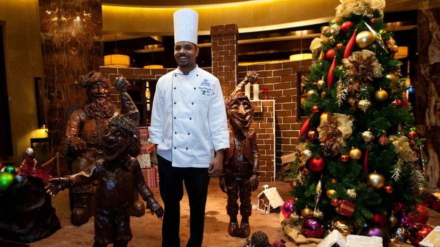 Award-winning Pastry Chef Mahesh Weerasinghe stands with his hand-sculptured, chocolate art at the Hilton Americas, Monday, Dec. 16, 2013, in downtown Houston. Chef Mahesh, along with the culinary and property operations teams, created a 1,000-pound Santa in his chair, accompanied by his elves and a wagon full of toys, all made from dark chocolate. The non-edible chocolate, after it was coated with a preserve, took more than 400 man hours and two months of work to create. (AP Photo/Houston Chronicle, Cody Duty)