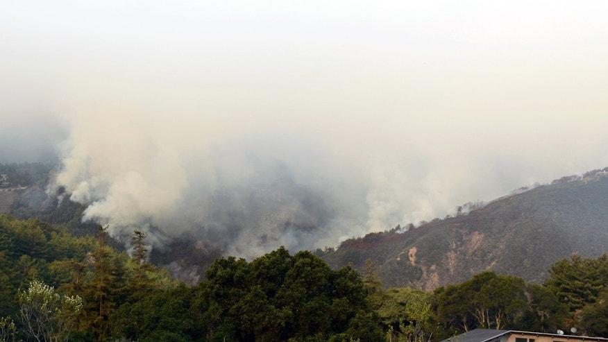 Smoke rises above Pfeiffer Ridge, Monday, Dec. 16, 2013, in Big Sur, Calif. The wildfire burning Monday in the Big Sur area of California destroyed at least 15 homes and forced about 100 people to evacuate as it chewed through dry vegetation on its way toward the ocean. (AP Photo/Nic Coury)