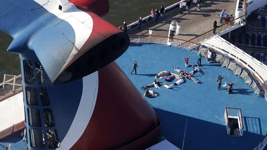 "FILE - In this Thursday, Feb. 14, 2013, file photo, passengers spell out the word ""HELP"" aboard the disabled Carnival Lines cruise ship Triumph as it is towed to harbor off Mobile Bay, Ala. (AP Photo)"