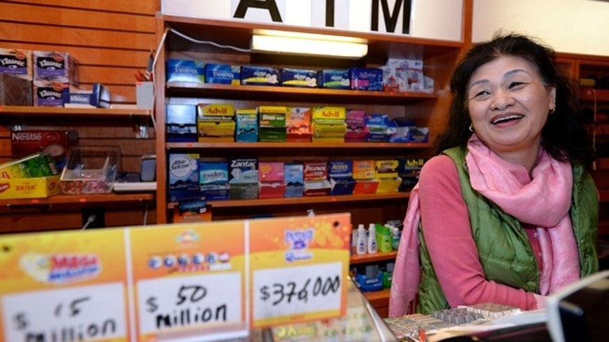 Dec. 18, 2013: Owner Young Soo Lee basks in the attention at her small Alliance Center office bulding newsstand in Atlanta, after lottery officials said one of two winning Mega Millions lottery tickets were purchased from her store in Tuesday's drawing.