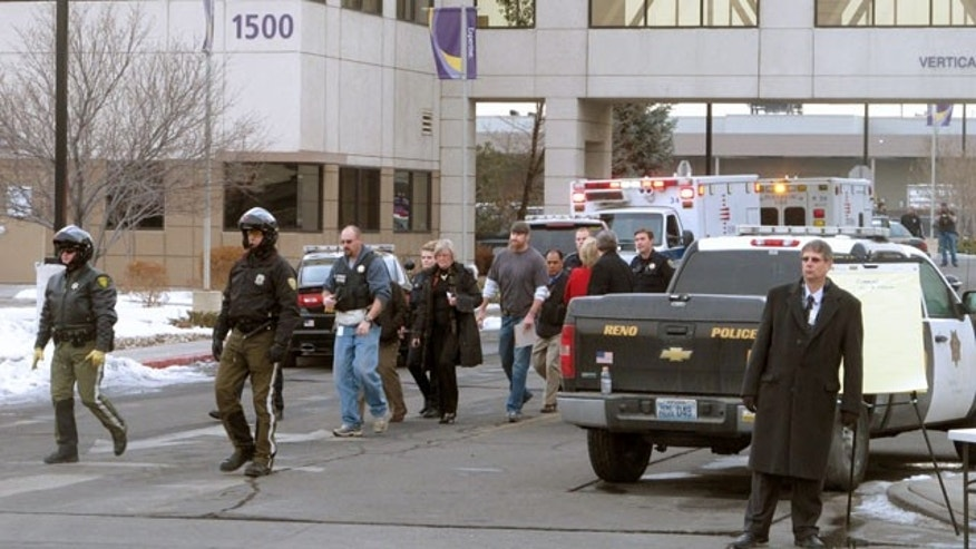 December 17, 2013: Police escort hospital staff members and others away from a medical office building in Reno, Nev. A suicidal gunman killed one person and critically wounded two others before turning the gun on himself on the grounds of the Renown Regional Medical Center Tuesday. (AP Photo/Scott Sonner).