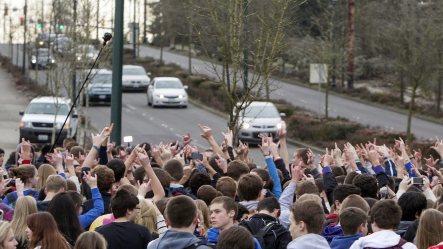 Students from Eastside Catholic High School yell to honking cars on Thursday, Dec. 19, 2013, in Sammamish, Wash. The students and faculty at the high school were protesting Thursday after learning their vice principal was asked to resign after school officials learned he had married his same-sex partner. (AP Photo/The Seattle Times, Steve Ringman)  SEATTLE OUT; USA TODAY OUT; MAGAZINES OUT; TELEVISION OUT; NO SALES; MANDATORY CREDIT TO: THE SEATTLE TIMES