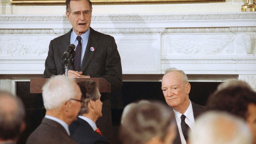 FILE - In this Tuesday, March 27, 1990, file photo, U.S. President George H. Bush, standing, addresses a White House luncheon commemorating former President Dwight. D. Eisenhower's 100th birthday. At right is John S.D. Eisenhower, the former president's son. John S.D. Eisenhower, the son of a five-star general turned president who forged his own career in the U.S. Army and then chronicled the history of the American military in numerous books, died Saturday, Dec. 21, 2013. He was 91. (AP Photo/Barry Thumma, File)