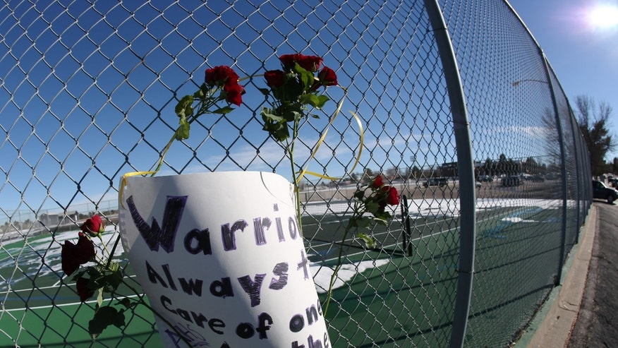Roses and a sign of support are woven into a cyclone fence around a tennis court at Arapahoe High School in Centennial, Colo., on Saturday, Dec. 14, 2013. The school was the scene of a shooting on Friday that left a student gunman dead and two other students injured. (AP Photo/David Zalubowski)