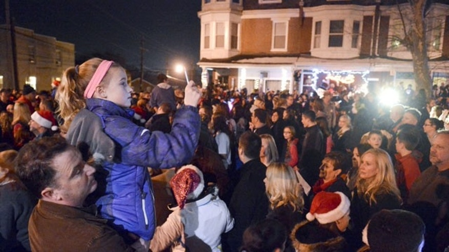 "December 21, 2013:Mike Simmons holds his daughter Gracie Simmons, 11, both of Wyomissing, while Gracie shoots video of the caroling in West Reading, Pa., where thousands of people came out to sing Christmas carols in front of the home of Delaney ""Laney"" Brown, 8, who is terminally ill with a rare form of leukemia. (AP Photo/Reading Eagle, Ben Hasty)"