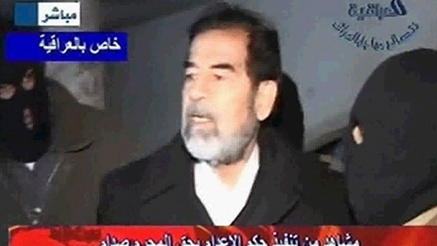 Dec. 30, 2006: A frame grab from Al Iraqiya television shows former Iraqi president Saddam Hussein speasking to his masked executors shortly before his hanging.