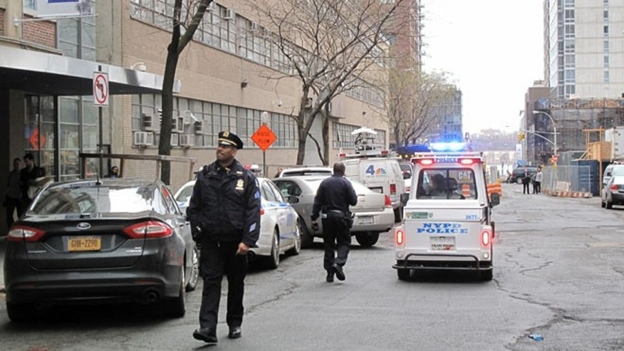 Dec. 22, 2013: In this photo, New York Police Department officers police walk in front of a high-rise apartment building where they said a 35-year-old man and a 3-year-old child  died after plummeting from the building in New York. The midtown Manhattan building, a short distance away from Columbus Circle and Lincoln Center,  is listed as South Park Tower, a rental. The circumstances of the fall are unclear. Authorities are investigating.