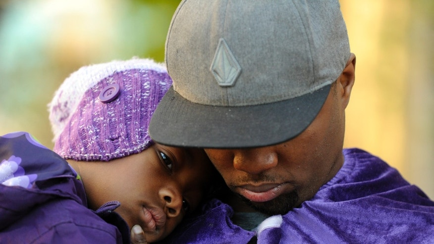 Quinton Reynolds, of Emeryville, wears a purple cape as he holds his daughter Qniyah Reynolds, 4, as he gathers with others outside of Children's Hospital Oakland in support of Jahi McMath in Oakland, Calif., on Monday, Dec. 23, 2013. McMath was declared brain dead after experiencing complications following a tonsillectomy at the hospital. (AP Photo/The Contra Costa Times-Bay Area News Group, Susan Tripp Pollard)