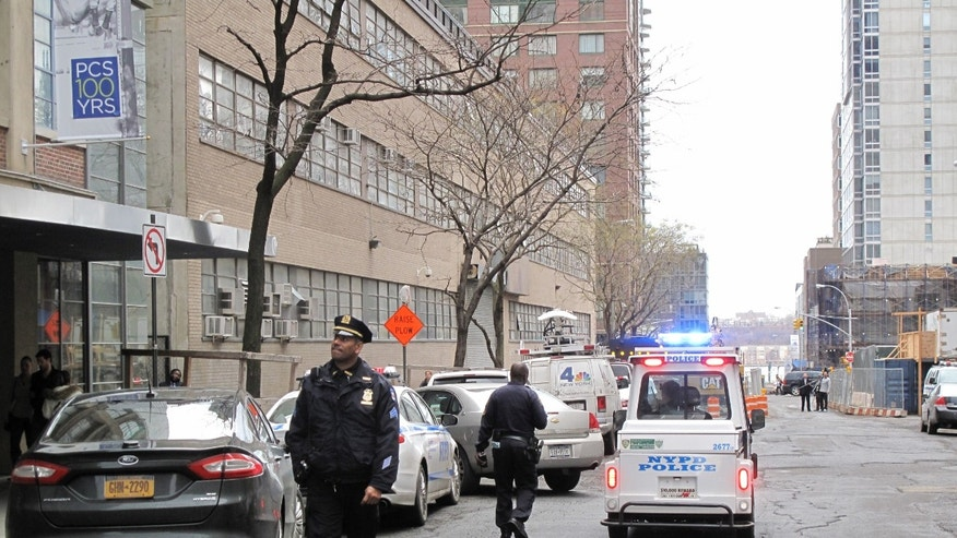 In this Sunday, Dec. 22, 2013 photo, New York Police Department officers police walk in front of a high-rise apartment building where they said a 35-year-old man and a 3-year-old child  died after plummeting from the building in New York. The midtown Manhattan building, a short distance away from Columbus Circle and Lincoln Center,  is listed as South Park Tower, a rental. The circumstances of the fall are unclear. Authorities are investigating. (AP Photo/Julie Walker)
