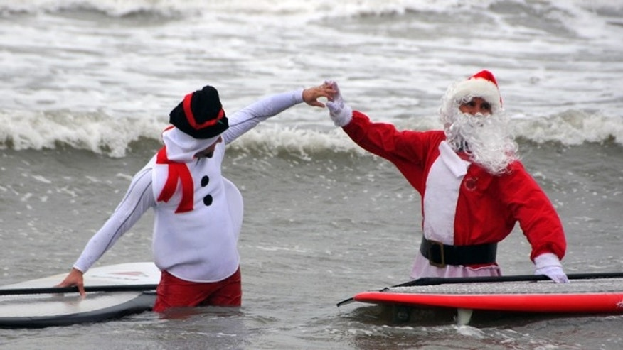 "Dec. 24, 2013: George Trosset Jr., dressed as a snowman, left, and his dad, event organizer George Trosset, high-five each other out in the waves during the fourth annual ""surfing Santas"" event in Cocoa Beach, Fla."