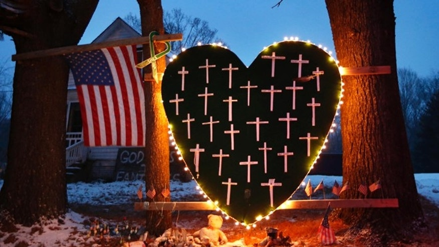 Dec. 14, 2013: In this file photo, a makeshift memorial with crosses for the victims of the Sandy Hook massacre stands outside a home in Newtown, Conn., the one-year anniversary of the shootings.