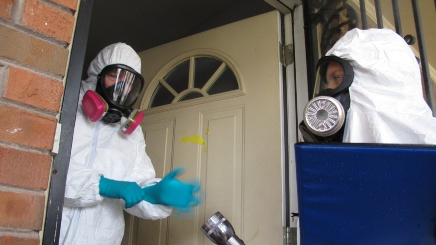 This Nov. 25, 2013 photo shows certified industrial hygienist Gary Siebenschuh, left, and assistant Courtney Van Stolk preparing to enter a house that was once used as a clandestine methamphetamine lab in Memphis, Tenn. The house was placed under quarantine after a Nov. 6 fire that police said was caused by a meth lab that exploded in the attic of the house. Siebenschuh and Van Stolk were hired by the homeowner to test the home for meth residue. (AP Photo/Adrian Sainz).