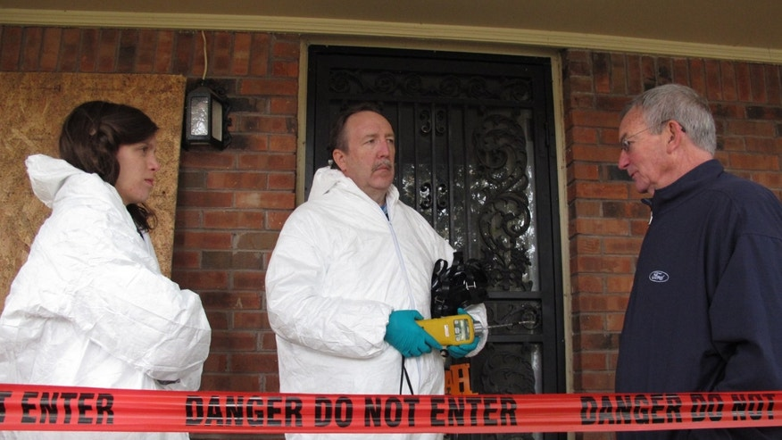 This Nov. 25, 2013 photo shows certified industrial hygienist Gary Siebenschuh, center, and his assistant Courtney Van Stolk, left, speaking with homeowner Dick Cochran after searching for  methamphetamine residue in the house he rents in Memphis, Tenn. The house was placed under quarantine after a Nov. 6 fire that police said was caused by a renter who was making meth in a clandestine lab that exploded in the attic of the house. (AP Photo/Adrian Sainz).
