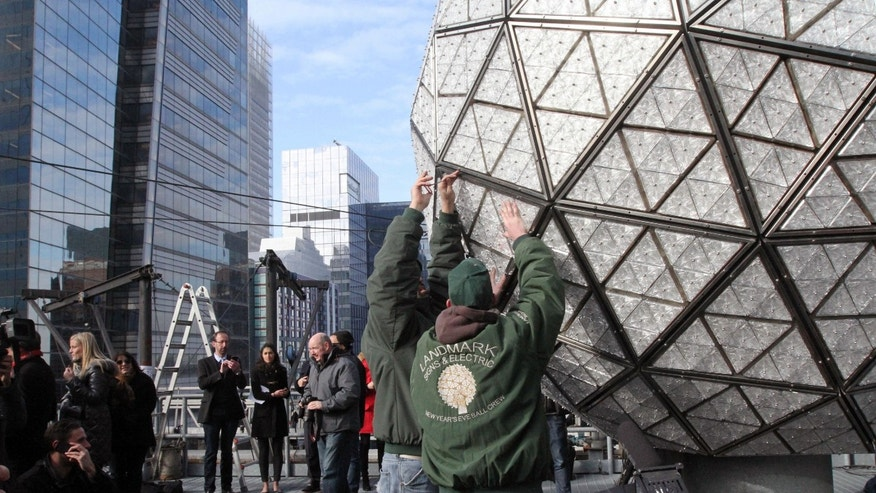Landmark Signs & Electric New Year's Eve Ball Crew members Nick Bonavita, standing foreground left, and Nick Russomanno, standing foreground right, install a Waterford crystal triangle on the New Year's Eve Ball during a media event Friday Dec. 27, 2013 on the roof of One Times Square in New York. (AP Photo/Tina Fineberg)
