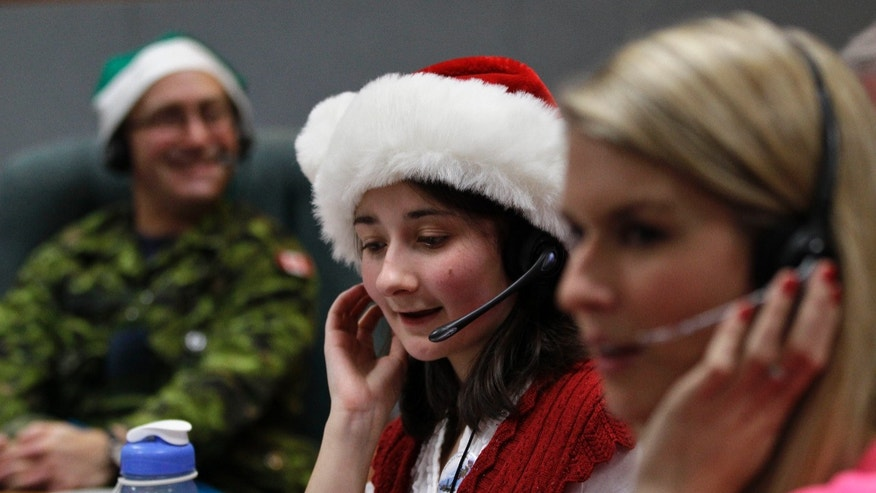 FILE - In this Dec. 24, 2012 file photo, volunteer Katherine Beaupre takes phone calls from children asking where Santa is and when he will deliver presents to their house,during the annual NORAD Tracks Santa Operation, at the North American Aerospace Defense Command, or NORAD, at Peterson Air Force Base, in Colorado Springs, Colo. The U.S. and Canadian military will entertain millions of kids again this Christmas Eve with second-by-second updates on Santa's global whereabouts. (AP Photo/Brennan Linsley, File)