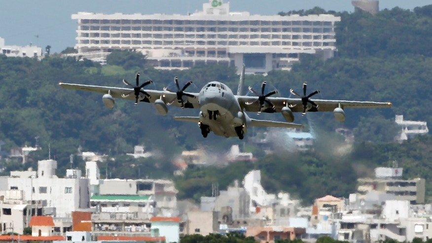 In this Aug. 16, 2012 photo, a C-130 transport plane takes off from the U.S. Marine Corps base in Futenma , in Okinawa, Japan. Okinawa Gov. Hirokazu Nakaima signed off Friday, Dec. 27, 2013, on the long-awaited relocation of the U.S. military base, a major step toward allowing the U.S. to move forward with plans to consolidate its troops in Okinawa and move some to Guam. Nakaima approved the Japanese Defense Ministry's application to reclaim land for a new military base on Okinawa's coast. It would replace the U.S. Marine Corps base in Futenma, a more congested part of Okinawa's main island. (AP Photo/Greg Baker)