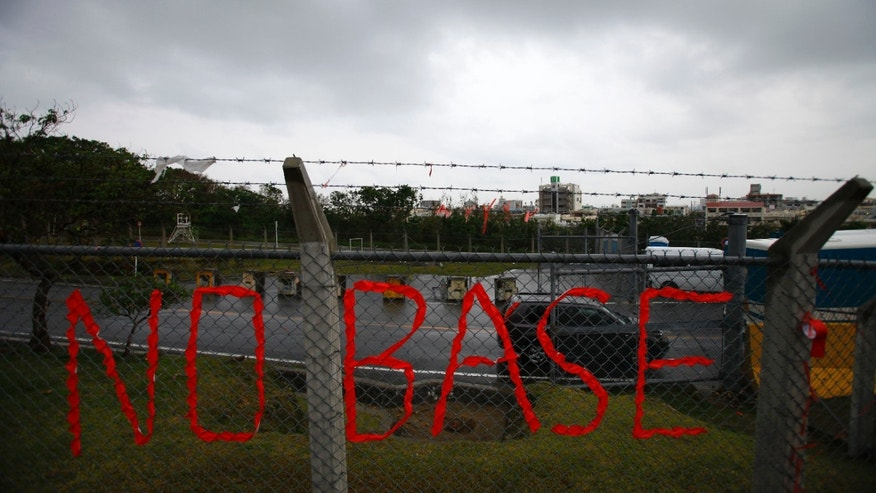 FILE - In this Nov. 30, 2012 file photo, a slogan against the base is displayed on the fence enclosed U.S. Marine Corps Futenma Air Station in Ginowan on southern Japanese islands of Okinawa. Okinawan Gov. Hirokazu Nakaima signed off Friday, Dec. 27, 2013, on the long-awaited relocation of the U.S. military base, a major step toward allowing the U.S. to move forward with plans to consolidate its troops in Okinawa and move some to Guam. Nakaima approved the Japanese government's application to reclaim land for a new base in Henoko of Nago city, which would replace Futenma Air Station, a more congested part of Okinawa's main island, Japanese media reported. (AP Photo/Junji Kurokawa, File)