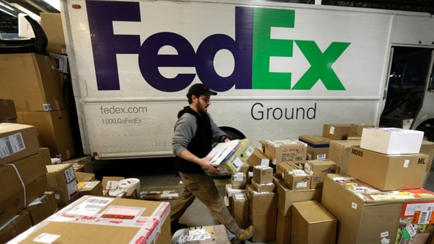 Dec. 16, 2013: In this file photo, package handler Chris Addison arranges packages before loading a delivery truck at a FedEx sorting facility in Kansas City, Mo.