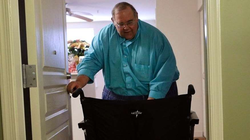Dec. 21, 2013: George Warren pulls his wheelchair through his apartment's front door at Village Crossroads, an affordable senior community in Nottingham, Md.