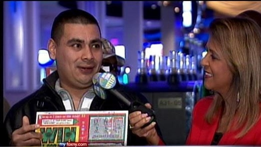 December 27, 2013: Marvin Martinez, left, speaks to a New York Lottery official after being announced as the official holder of a $1M ticket he found after Superstorm Sandy (MyFoxNY.com)