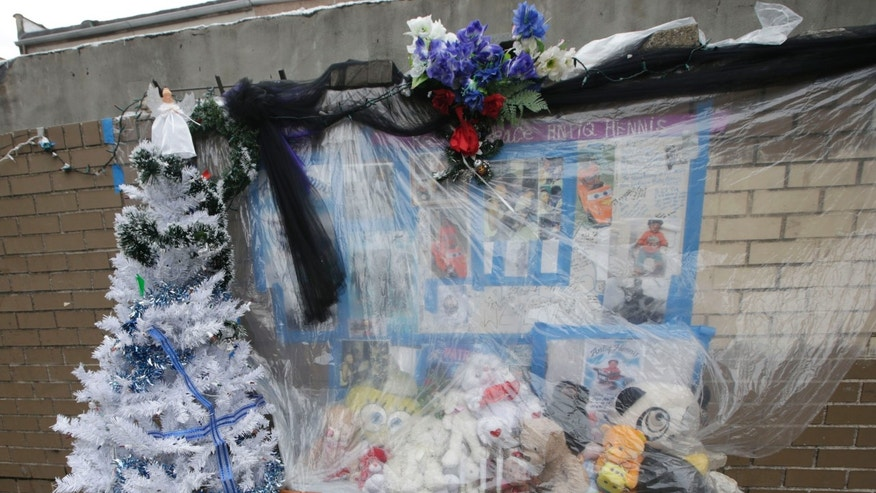 A memorial to slain one-year-old Antiq Hennis is covered plastic at the Marcus Garvey Village apartments in the Brownsville section of the Brooklyn borough of New York on Monday, Dec. 30, 2013. Hennis was shot in the head Sept. 1 as his stroller was wheeled across a street.  Police believe the boy's father was the intended target, but the father refused to cooperate in identifying the shooter.  Year-end boasts by Mayor Michael Bloomberg that New York is the safest big city in America ring hollow in Brooklyn's Brownsville, a neighborhood of entrenched gang violence that has proven stubbornly immune to strategies that have pushed crime to historic lows across the rest of the city. (AP Photo/Kathy Willens)