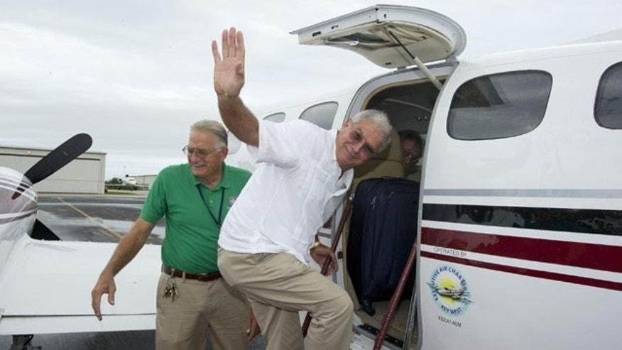 In this photo provided by the Florida Keys News Bureau, Key West December 30, 2013: Mayor Craig Cates, right, waves goodbye as he boards a chartered aircraft at Key West International Airport that flew to Havana, Cuba. The trip was the first legal commercial passenger flight from Key West to Cuba in more than 50 years and carried passengers who will remain until Jan. 3, 2014. (AP/Florida News Bureau)