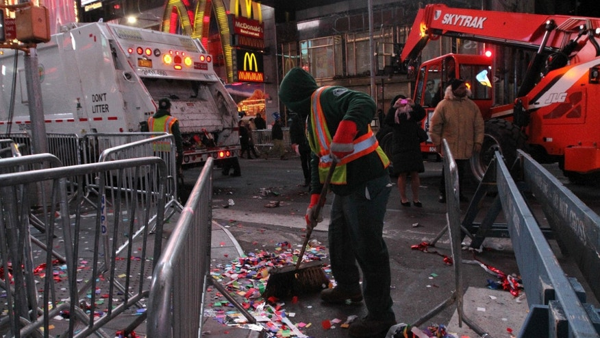 A sanitation worker sweeps up debris in New York's Times Square early New Year's Day Wednesday Jan. 1, 2014. (AP Photo/Tina Fineberg)