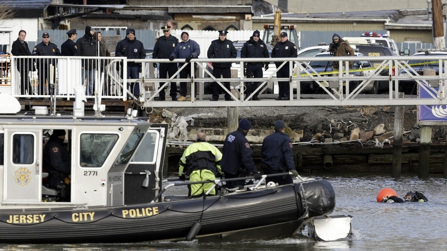 Workers in dive gear, bottom right, work the scene while trying to recover a vehicle that was allegedly driven into the Morris Canal at Liberty Harbor in Jersey City, N.J., Wednesday, Jan. 1, 2014. The body of the 22-year-old driver was recovered shortly after authorities responded to the scene of the crash, which was reported around 3:30 a.m. (AP Photo/Julio Cortez)