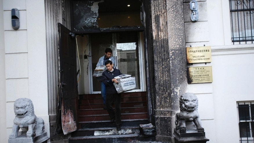 Jan. 2, 2014: Workers carry stacks of newspaper from the steps of the damaged front of the Chinese consulate after an unidentified person set fire to the main gate in San Francisco, California.