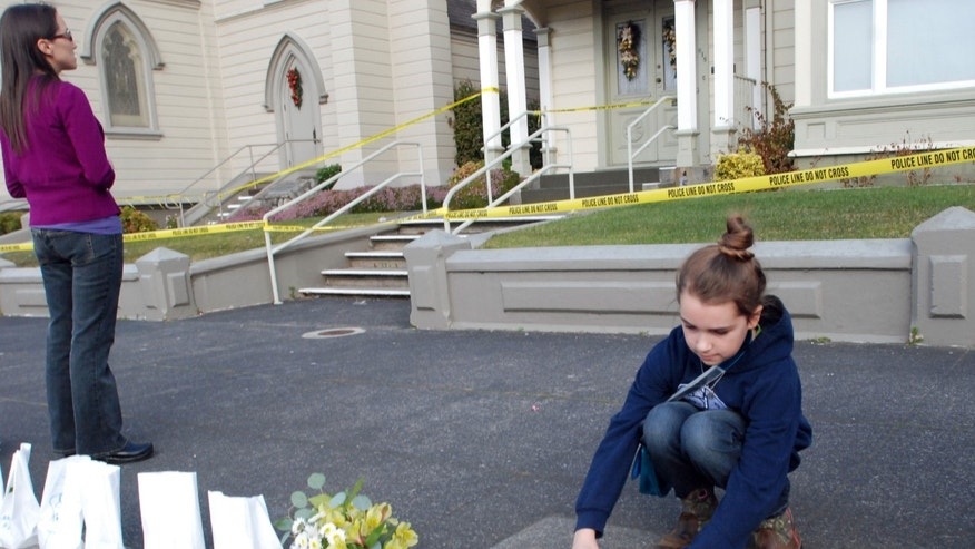 Amanda Enemark lays flowers at an impromptu shrine while Lauire Lynch prays Thursday, Jan. 2, 2014, outside St. Bernard Catholic Church rectory in Eureka, Calif., where Fr. Eric Freed was found slain on New Year's Day. Police arrested a man Thursday in the slaying. He was identified as Gary Lee Bullock, 43, of Redway, Calif. (AP Photo/Jeff Barnard)