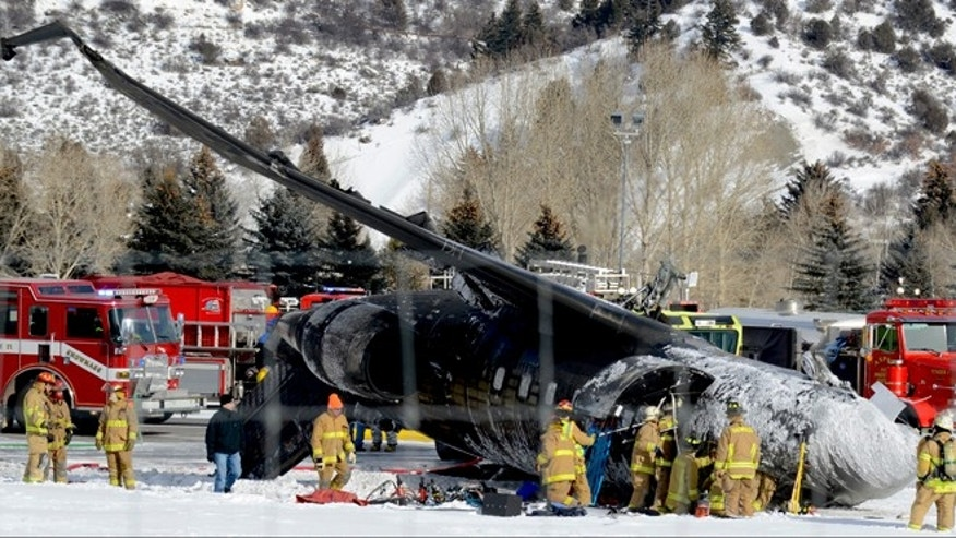 Jan. 5, 2014: Emergency crews work near a plane that crashed upon landing at the Aspen-Pitkin County Airport in Aspen, Colo.