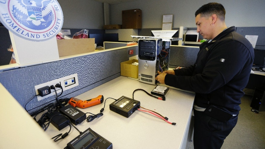 Army Staff Sgt. Oskar Zepeda removes a hard drive from a computer seized as evidence, Monday, Dec. 16, 2013, at a Digital Forensics Lab at an Immigration and Customs Enforcement field office in Seattle, where he is serving a one-year internship. Zepeda, who served nine tours of duty in Iraq and Afghanistan, before being wounded, is part of a 17-member class of veterans deployed to ICE field offices throughout the country to use his newly acquired skills in computer forensics to help capture and prosecute child predators. (AP Photo/Ted S. Warren)