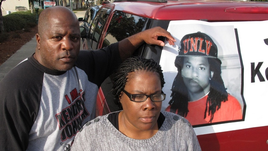 Kenneth and Jacquelyn Johnson stand next to a banner on their SUV showing their late son, Kendrick Johnson, on Dec. 13, 2013, in Valdosta, Ga. The 17 year old was found dead inside a rolled up gym mat at his high school Jan. 11, 2013, and authorities ruled it was a freak accident. Kendrick's family believes someone killed him and has been fighting to reopen the case. (AP Photo/Russ Bynum)