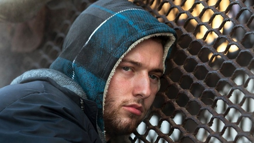 Jan. 4, 2014: Nicholas Simmons, 20, of Greece, N.Y.,  warms himself on a steam grate with three homeless men by the Federal Trade Commission, in Washington.