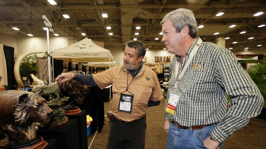 Jan. 8, 2014: Dallas Safari Club executive director Ben Carter, right, talks with wildlife artist Raj S. Paul at his exhibit booth in the Dallas Convention Center.